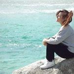 Autora del testimonio sentada en una roca frente al mar