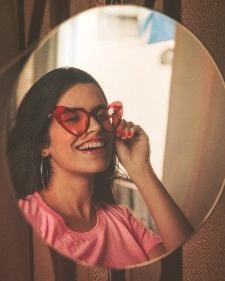 Chica sonríe mirándose al espejo