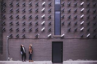 Dos personas enfocadas por muchas videocámaras.