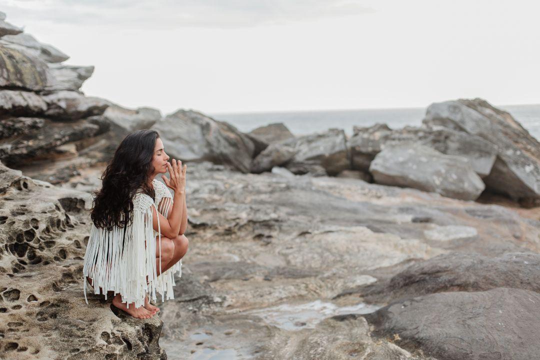 Mujer meditando entre las rocas.